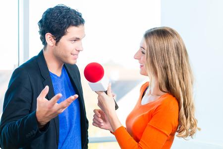 Vrouw Radio gastheer doet interview met gastatelier in radiostation tijdens een show voor radio wonen in de Studio