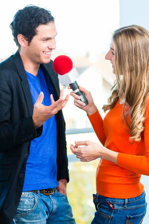 interviewing: Female Radio host doing interview with Studio guest in radio station during a show for radio live in the Studio