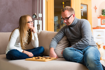 game room: Father and daughter playing parlor or board game checkers on sofa Stock Photo