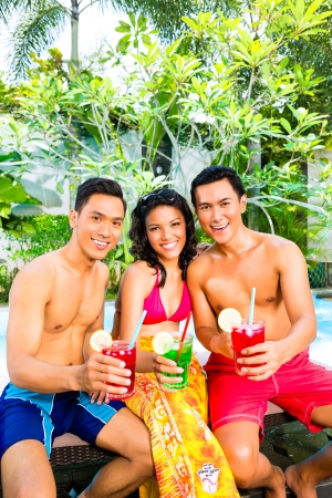 Asian friends drinking fancy cocktails at hotel or club pool photo