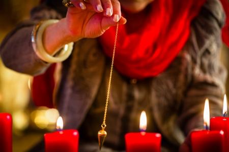 adivino: Mujer adivino o esotérica Oracle, ve en el futuro por su radiestesia péndulo durante una sesión de espiritismo para interpretarlos y para responder a las preguntas Foto de archivo