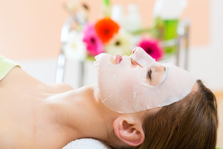 beauty therapist: Wellness - woman receiving facial mask in spa for clean skin Stock Photo