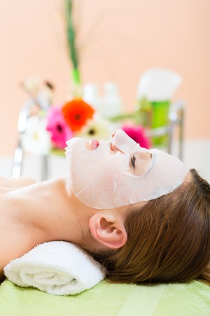 masks: Wellness - woman receiving facial mask in spa for clean skin Stock Photo