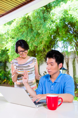 annoying: Chinese mother brings her son some food, he makes homework for the next day at school and is concentrated Stock Photo