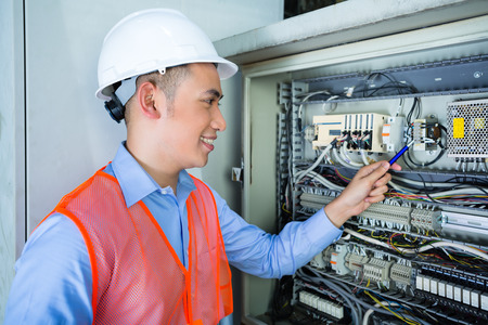cabling: Asian Indonesian Technician or electrician making function test on breaker box or switchbox with power lines on construction site or in factory for acceptance