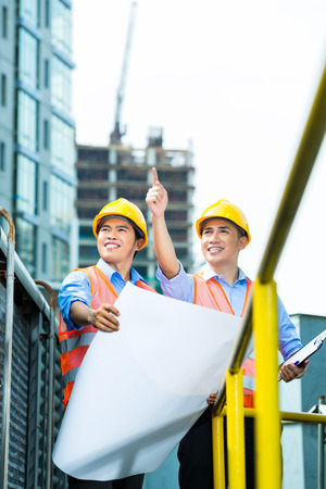 Asian Indonesian construction workers with blueprint or plan on building site Stock Photo