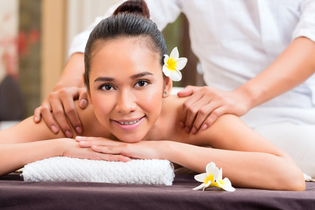 Indonesian Asian woman in wellness beauty day spa having aroma therapy massage with essential oil, looking relaxed photo