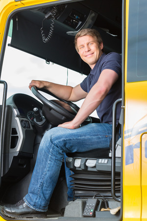 Logistik - stolt förare eller skotare i drivrutiner locket på bil och släp, vid en omlastningspunkt