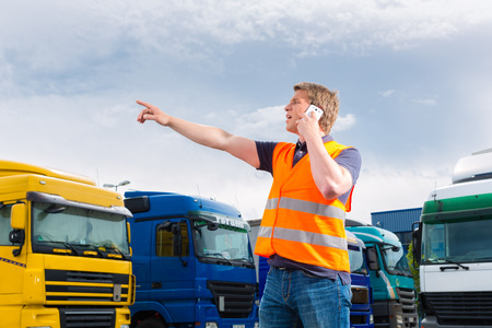 forwarder: Logistics - proud driver or forwarder with mobile phone in front of trucks and trailers, on a transshipment point