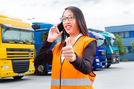 Logistics - female Asian forwarder or supervisor with mobile phone, in front of trucks and trailers, on transshipment point photo