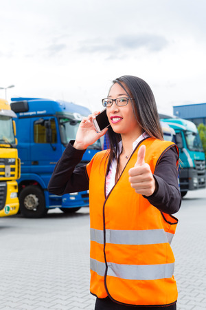 convinced: Logistics - female Asian forwarder or supervisor with mobile phone, in front of trucks and trailers, on transshipment point
