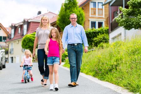 ni�os caminando: Familia joven con la madre, padre e hijas que recorren a trav�s de un conjunto habitacional, tal vez hacer un viaje o excursi�n de la tarde Foto de archivo