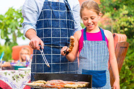 Father and daughter making barbecue in the garden in summer with sausages and meat photo