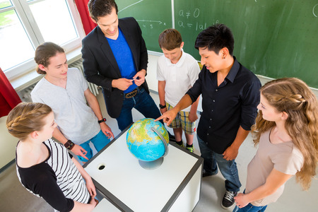 human geography: School Students or pupils or mates having group work while geography lesson and the teacher test or educate them in school or class