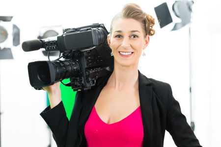 Camerawoman or Cameraman or shooting  with digital camera on film set or video production for TV or television  or News  photo