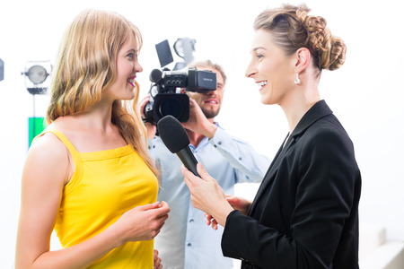 Periodista y camarógrafo rodaje entrevista la actriz en el set de película para la televisión o la televisión Foto de archivo - 25769362