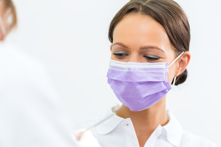 dentist in her practice or office treating male patient with assistant wearing mask photo