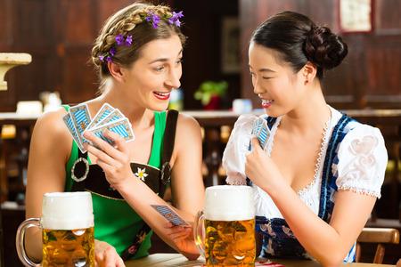 lederhosen: In Pub - friends in Tracht, Dirndl and Lederhosen drinking a fresh beer in Bavaria, Germany playing cards