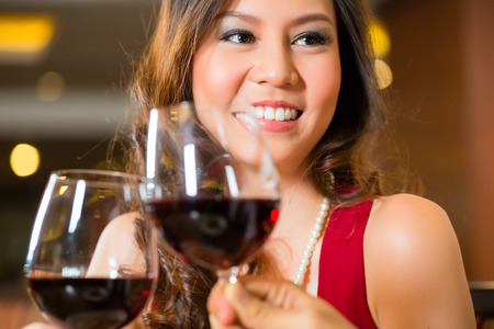 Man and woman or couple toasting on a date or a romantic dinner in a fancy restaurant with red wine in glasses photo