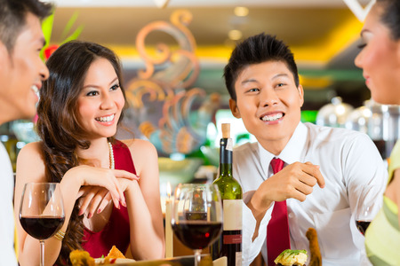 Four Asian Chinese business people having dinner in elegant club restaurant or hotel Stock Photo