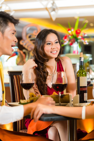 Four Asian Chinese business people having dinner in elegant club restaurant or hotel photo