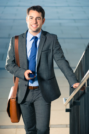 Handsome businessman or manager using phone and going to business appointment or home photo