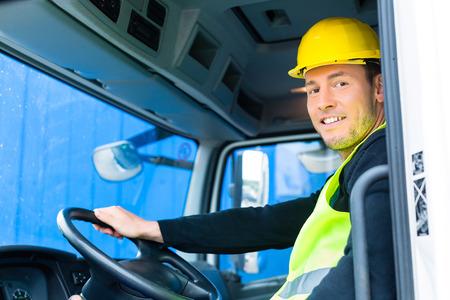 camion grua: conductor a conducir con el camión sobre la construcción o emplazamiento de la obra Foto de archivo