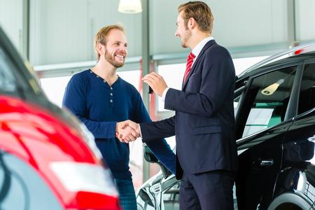 Verkoper of autoverkoper en klant in auto dealer, ze handen schudden, overhandigt de autosleutels en sluit de aankoop van de auto of nieuwe auto