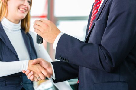 Seller or car salesman and customer in dealership, they shaking hands, hands over the car keys and seal the purchase of the auto or new car photo