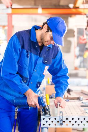 compressed air: Craftsman rivet metal with air compressed pistol in workshop