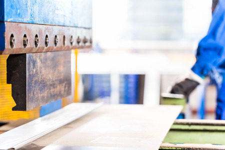 forming: Craftsman forming metal with skip in workshop