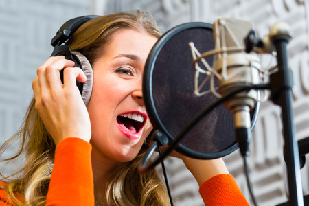 recording studio: Young female singer or musician with microphone and headphone for audio recording in the Studio Stock Photo
