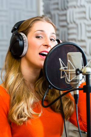 music production: Young female singer or musician with microphone and headphone for audio recording in the Studio Stock Photo