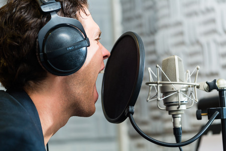 music production: Young male singer or musician with microphone and headphone for audio recording in the Studio Stock Photo