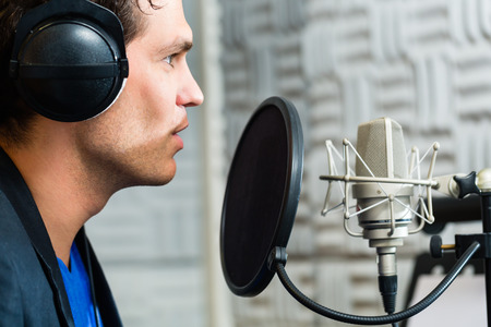 Young male singer or musician with microphone and headphone for audio recording in the Studio Фото со стока