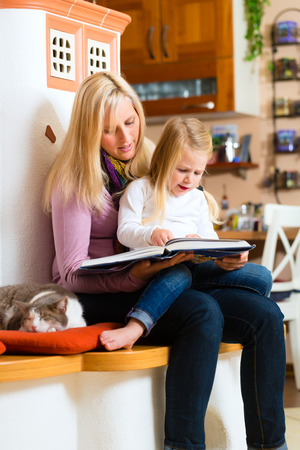 Mother reading tired daughter good night story out of storytelling book photo