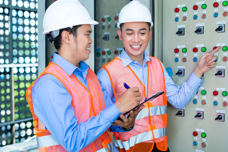 acceptance: Asian Indonesian Technician or electrician making function test on Panel or switchbox for the control of air conditioners on construction site or in factory for acceptance