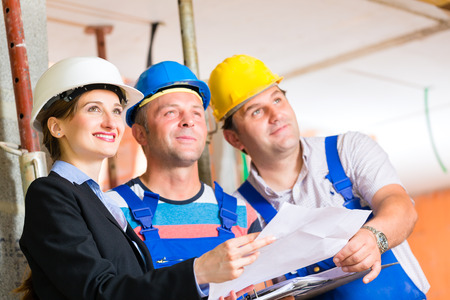 tallyman: Construction site team or architect and builder or worker with helmets controlling or having discussion of plan or blueprint  Stock Photo