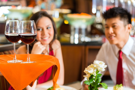 Waiter or steward serving man and woman or couple red wine in glasses on a tray in a fancy restaurant or hotel Stock Photo - 25816124