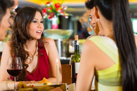 business: Four Asian Chinese business people having dinner in elegant club restaurant or hotel Stock Photo