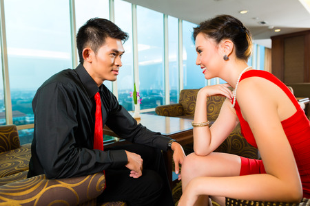 upscale: Young and handsome couple flirting in a luxurious and fancy lounge or hotel sky bar Stock Photo