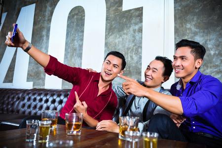 personas festejando: La gente del partido Asian grupo de jóvenes amigos tomando fotos o selfies con su teléfono móvil o celular en la fantasía club nocturno