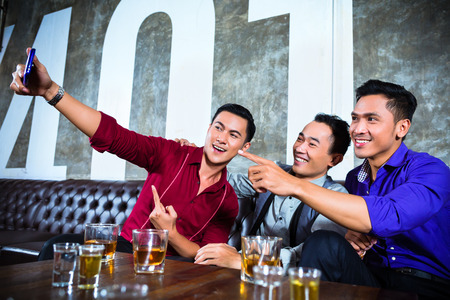 club: Persone di partito Asian gruppo di giovani amici, scattare foto o selfies con il proprio telefono cellulare o un cellulare in night club di fantasia