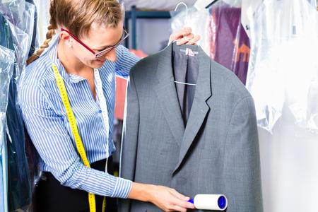 Vrouw schoner in wasserij winkel controleren van schone kleren verwijderen pluisjes met rol