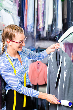 dry cleaner: Female cleaner in laundry shop checking clean clothes removing lint with roller