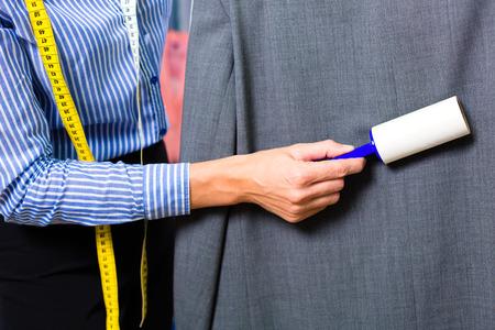 personal de limpieza: Limpiador Mujer en la tienda de la ropa de cheques ropa limpia quitando la pelusa, rodillo Foto de archivo