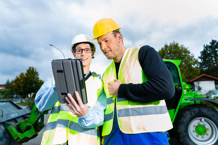 Construction worker and engineer on site discussing blueprints on pad or tablet computer, excavator and other construction machinery photo