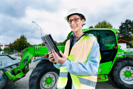 female construction worker: Architect or engineer on site checking blueprints on pad or tablet computer, excavator and other construction machinery