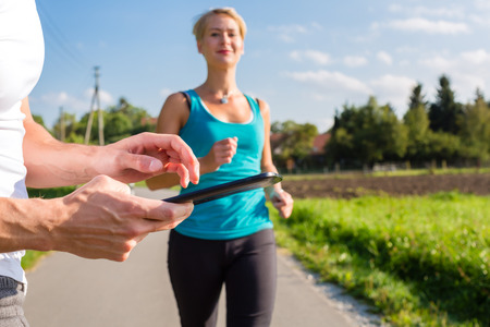 woman doing jogging or outdoor running sport for fitness on\ rural street, the trainer stopping her time with app on tablet\ computer