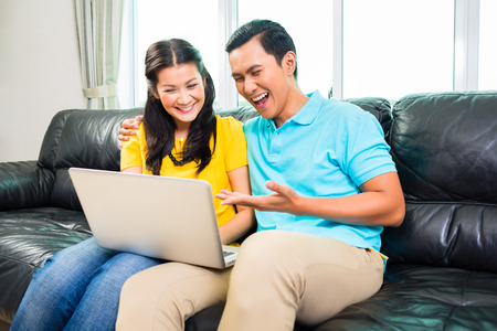 Young Asian handsome couple using laptop on couch at home photo